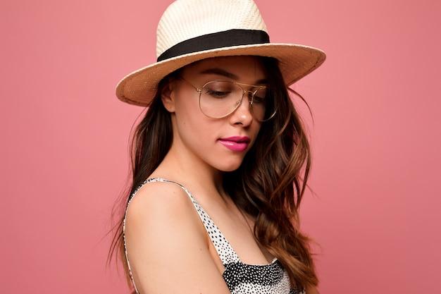 Привлекательная милая женщина с волнистыми волосами в шляпе и очках с розовыми губами позирует на розовой стене