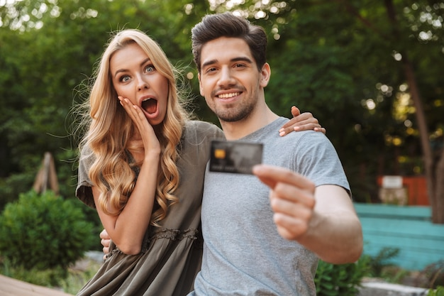 Attractive lovely young couple looking at the camera and posing with credit card while woman in shock