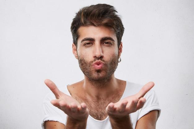 Attraente uomo macho con i capelli scuri e la barba che soffia bacio e si tiene per mano davanti a sé. brunet attraente che flirta inviando un bacio