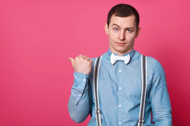Attractive male in blue shirt, suspenders and white bow tie, shows with thumb finger aside
