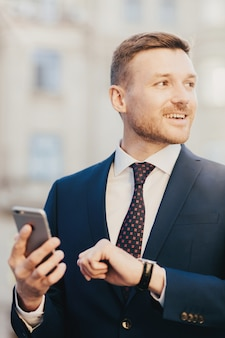 Attractive male comes on meeting with client, looking at watch and holds smart phone