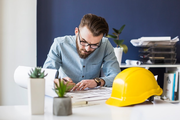Attractive male engineer drawing plan on blueprint at workplace