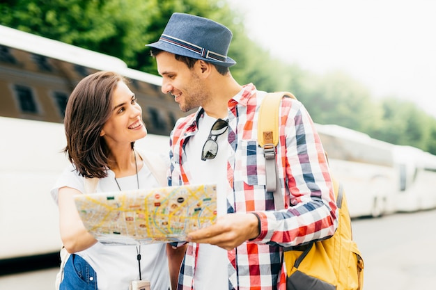 Attractive male and female tourists, being in unfamiliar place, holding map or city guide, deciding where to go first, looking happily at each other, standing near tourists` bus. travelling concept