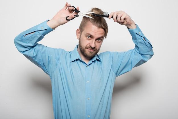 魅力的な男性美容師ははさみと櫛で身をかがめる