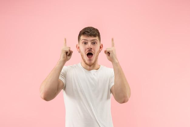 ピンクのスタジオの背景に魅力的な男性のハーフレングスの正面の肖像画。口を開けて立っている若い感情的な驚きのひげを生やした男。