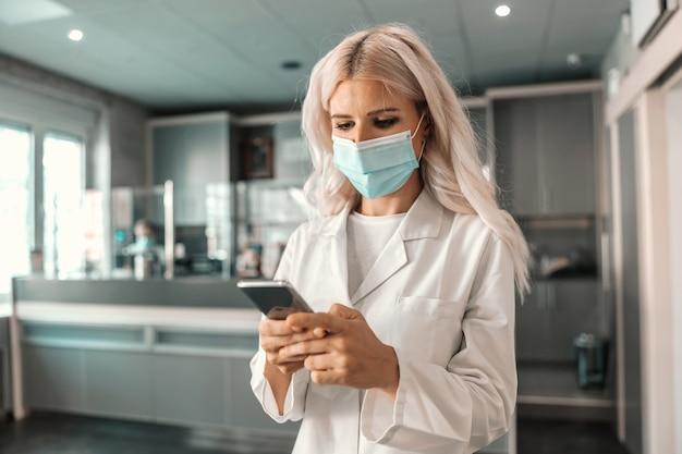 실험실 홀에 서서 환자에게 양식을주는 매력적인 남성 실험실 조교. 그녀는 코로나 바이러스 검사를받을 것입니다.
