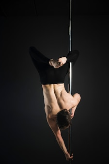 Attractive male model performing a pole dance