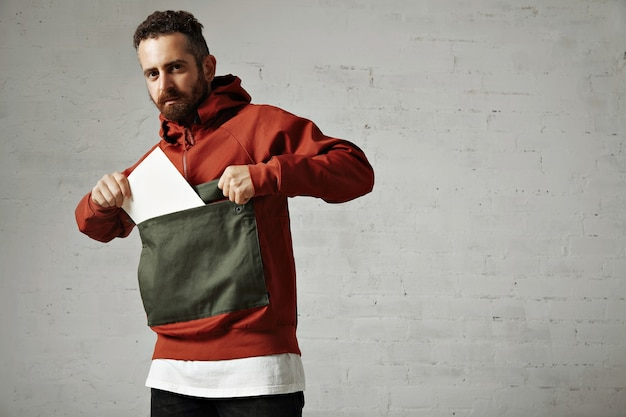 Attractive male model taking a blank white sheet of paper out of the front pocket of his red and gray parka on white