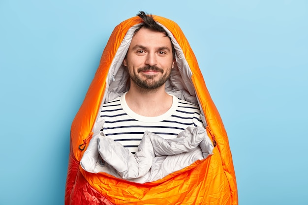 Attractive male model with dark beard and mustache, poses in comfortable sleeping bag, being on summer holidays near river, sleeps in tent, spends night under sky, isolated over blue wall