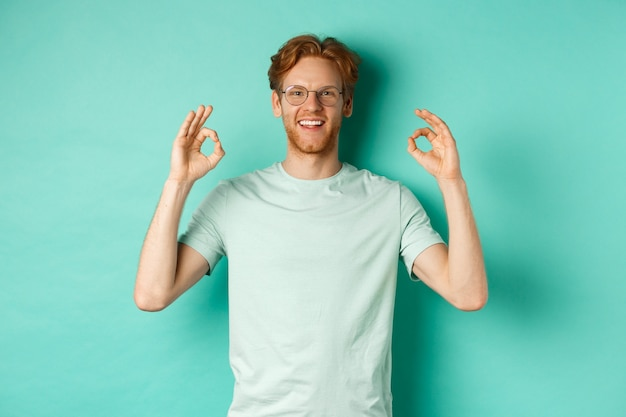 赤い髪の魅力的な男性モデル、眼鏡をかけ、承認のokサインを示し、「はい」と言って、満足のいく笑顔で、ミントの背景の上に立っています。