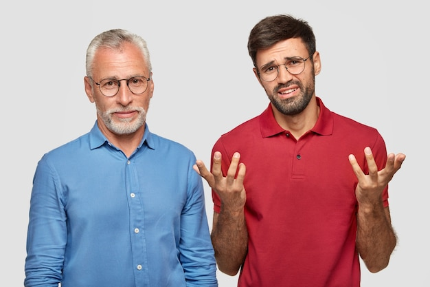 Attractive male pensioner cooperates together with his young colleague who has desperate nervous expression, stand next to each other, isolated over white wall. people and relationships