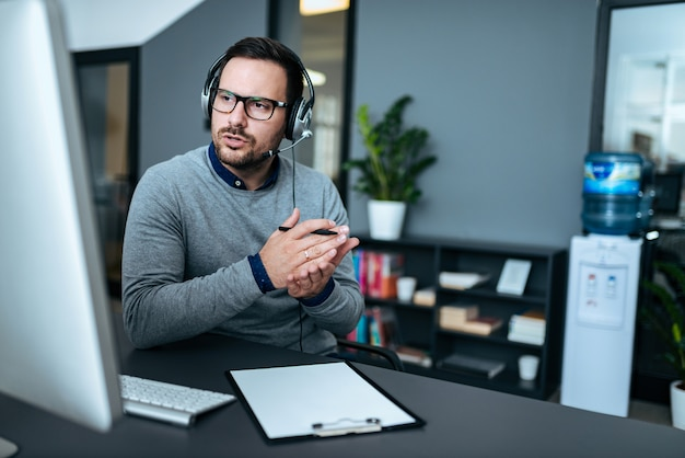 Attractive male support center agent with headset on talking to client.