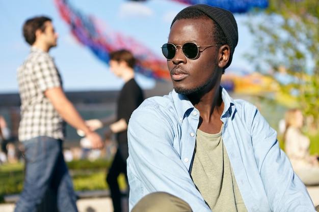 暗い純粋で健康的な肌と剛毛を持ち、色合いとシャツを着て、屋外に座っている間真剣に脇を見ている魅力的な男性