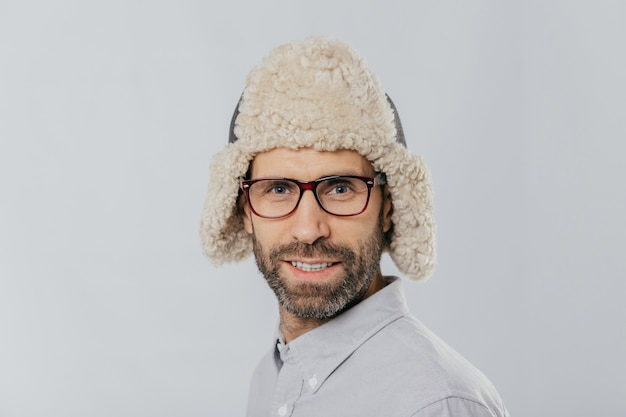 Attractive male with stubble, wears glasses and fur hat