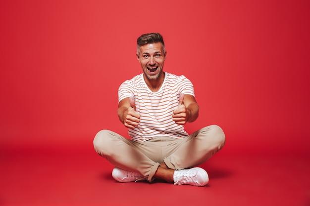 Привлекательный мужчина 30 лет в полосатой футболке улыбается, сидя на полу со скрещенными ногами, изолирован на красном