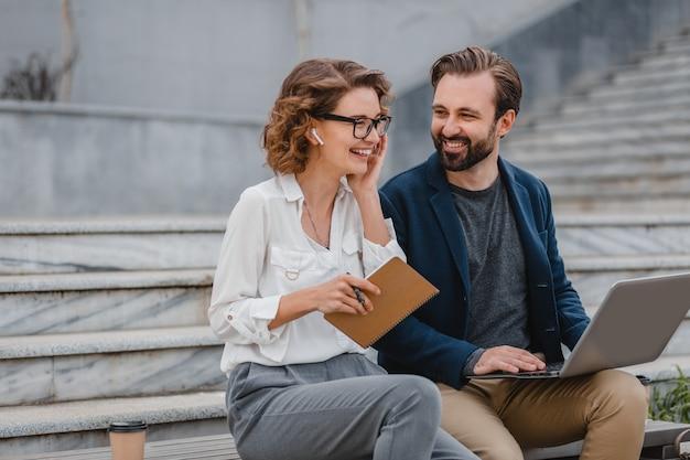 Привлекательный мужчина и женщина, сидя на лестнице в центре города, вместе работая над ноутбуком