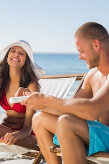 Attractive man applying sun cream on his girlfriend
