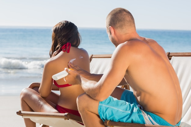 Attractive man applying sun cream on his girlfriends back