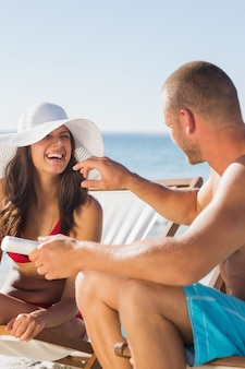 Attractive man applying sun cream on his girlfriends nose