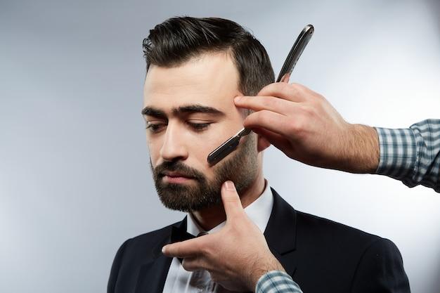 이발소에서 매력적인 남자, 아래를 내려다 보면서, 스튜디오 배경에서 검은 머리를 가진 남자를위한 수염 형태를 만드는 셔츠를 입고 남자의 손, 초상화.