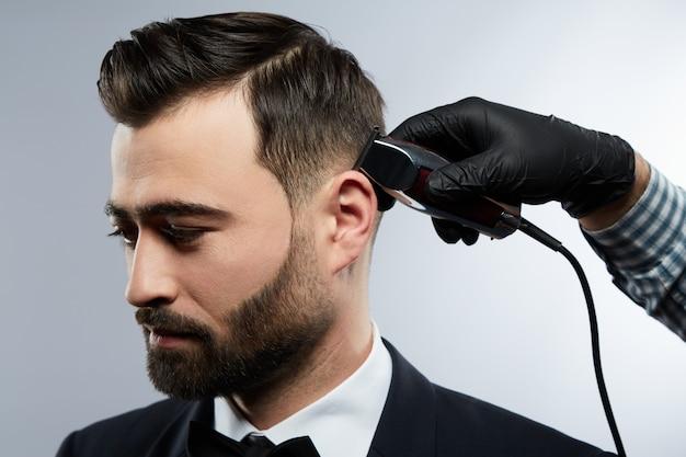 이발소에서 매력적인 남자, 아래를 내려다 보면서, 스튜디오 배경에서 검은 머리를 가진 남자를위한 트리머로 머리를 자르는 셔츠를 입고 남자의 손, 초상화.