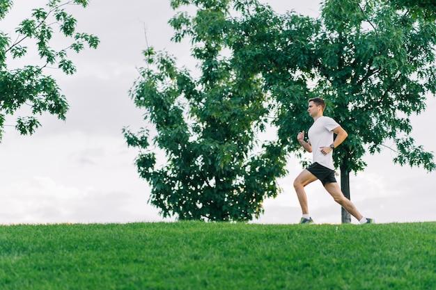 Attractive man athlete wearing sportswear run in park at summer. copyspace.