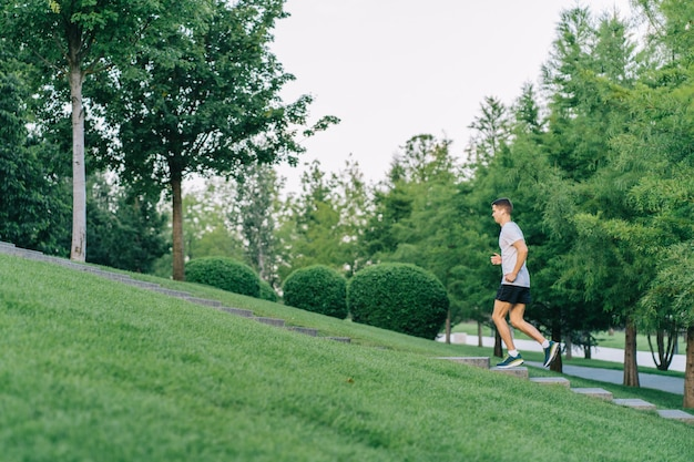 Attractive man athlete wearing sportswear run in park at summer up the stairs.
