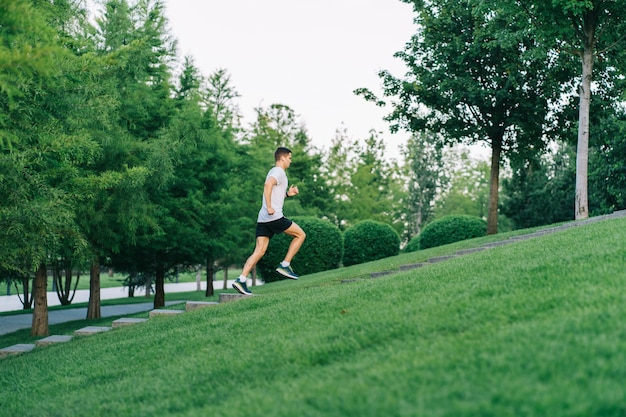 Attractive man athlete wearing sportswear run in park at summer up the stairs