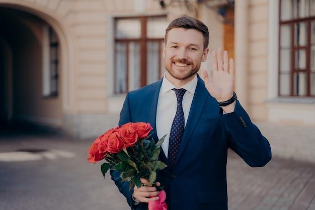 赤いバラの花束と一人で立っている青いスーツに身を包んだ魅力的な男性ビジネスパーソン