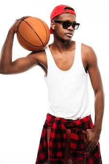 Uomo attraente in protezione ed occhiali da sole che tengono la sfera di pallacanestro