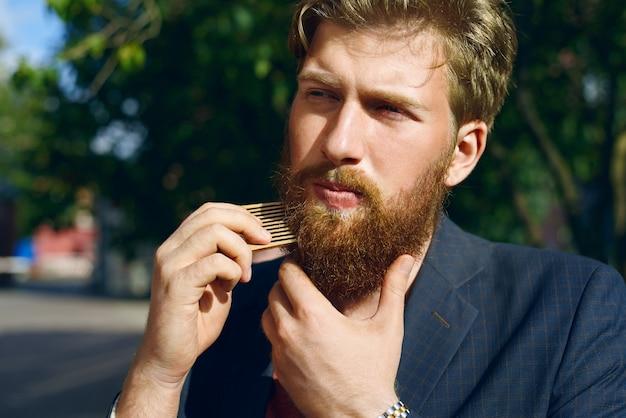 Привлекательный мужчина расчесывает бороду