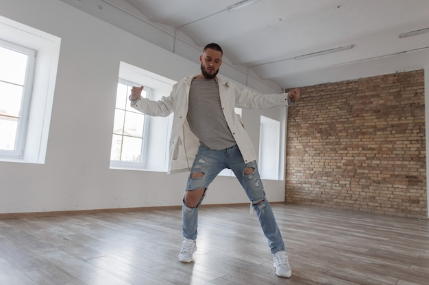 댄스 스튜디오에서 춤을 추는 세련된 옷을 입고 매력적인 남자 댄서