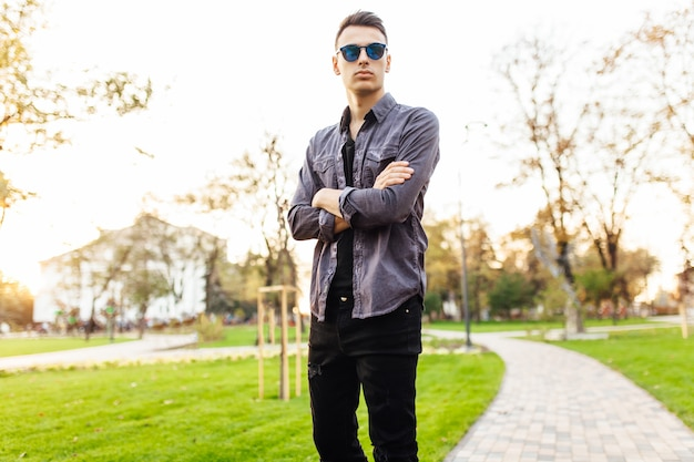 Attractive man dressed in stylish clothes, sunglasses, walks in the park, against the sunset