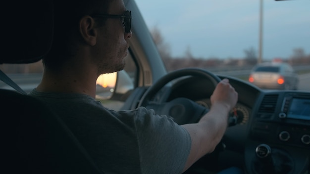 The attractive man driving the auto along the urban highway