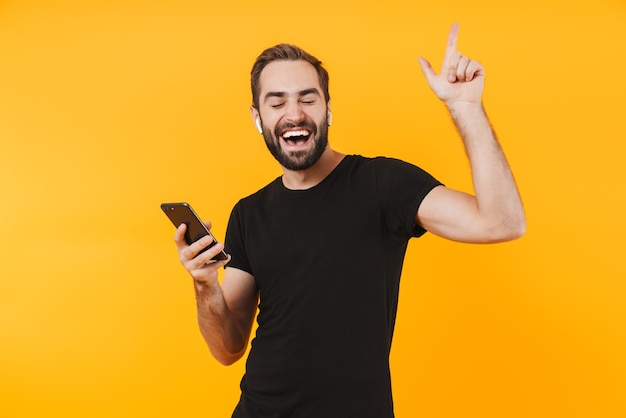 Attractive man in earpods dancing and listening to music with cellphone isolated over yellow wall