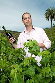 포도원에서 하루를 즐기고 좋은 와인을 즐기는 매력적인 남자