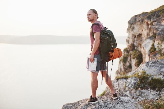 Привлекательный человек, наслаждаясь видом на горы пейзаж над поверхностью воды. концепция путешествий и путешествий