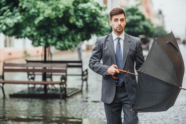魅力的な男が傘を持って通りを下り、正面を見る