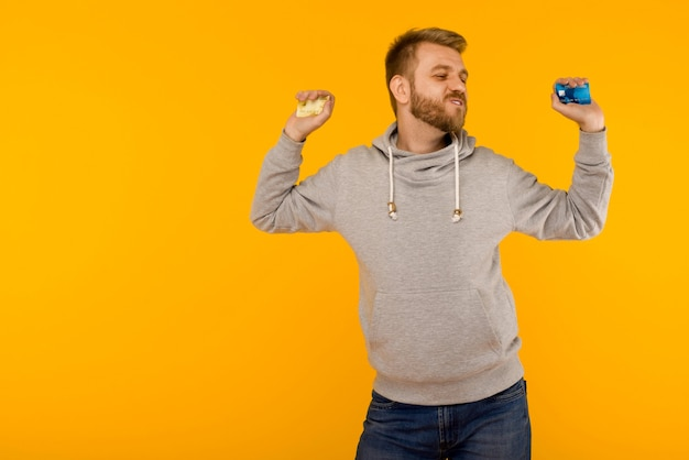 Attractive man in a gray sweatshirt joyfully dances with a credit card in his hand on a yellow background - image