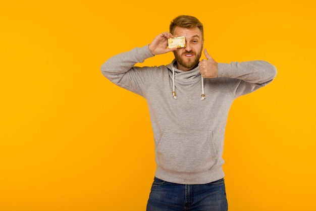 Attractive man in a gray sweatshirt raised a finger up holds a credit card in his hand on a yellow background - image