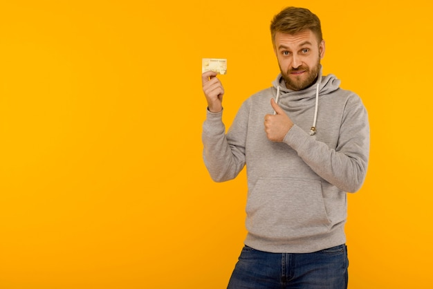 Attractive man in a gray sweatshirt raised a finger up holds a credit card in his hand on a yellow background