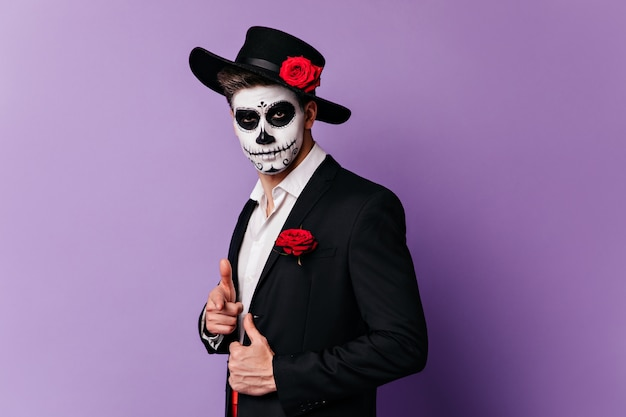 Attractive man in halloween mask poses in classic outfit on purple background.