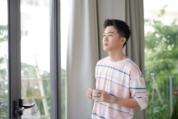 Привлекательный мужчина, пьющий чай в своей гостиной