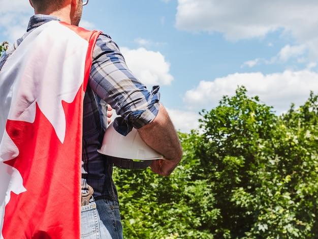 晴れた日に青い空を背景にカナダの旗を保持している魅力的な男性。後ろから見たクローズアップ。国民の祝日のコンセプト