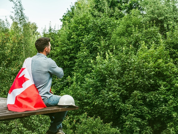 Attractive man holding canadian flag on blue sky on a clear, sunny day. view from the back, close-up. national holiday concept
