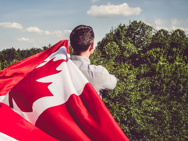 Attractive man holding canadian flag. national holiday