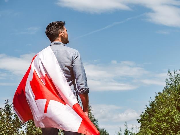 맑고 화창한 날에 푸른 하늘 배경에 캐나다 국기를 들고 매력적인 남자. 뒤에서보기, 클로즈업. 공휴일 개념