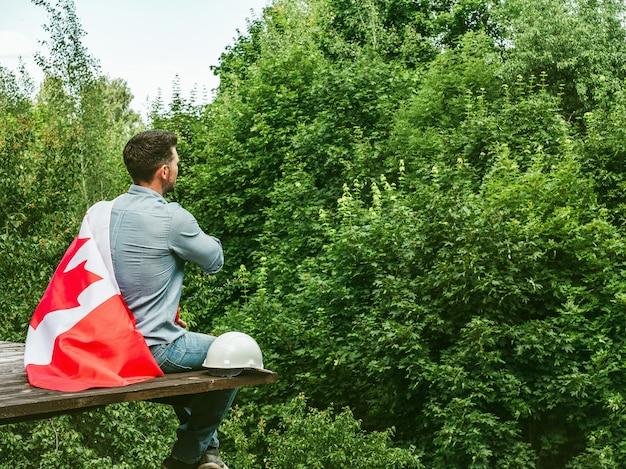 澄んだ晴れた日に青い空にカナダの旗を保持している魅力的な男性。後ろから見たクローズアップ。国民の祝日のコンセプト