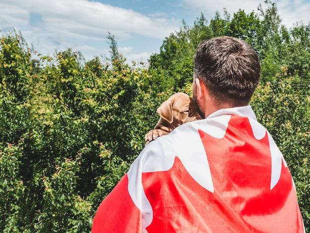 매력적인 남자는 맑고 화창한 날 푸른 하늘을 배경으로 매력적인 강아지를 안고 있습니다. 야외, 클로즈업. 국경일 개념