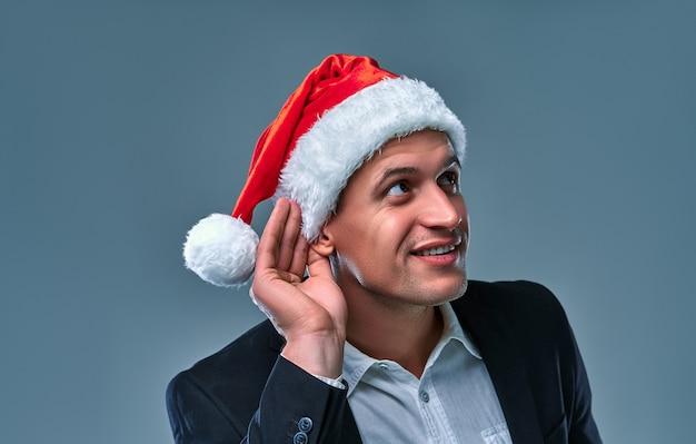 크리스마스 모자를 쓴 매력적인 남자가 손을 귀에 대고 스튜디오의 회색 배경을 엿듣습니다.